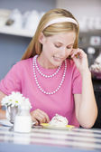 A young woman sitting in a cafe eating a sweet treat — Stock Photo