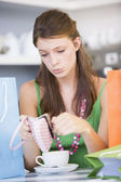 A young woman sitting in a cafe looking sadly into her purse — Stock Photo