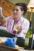 A young woman in her pyjamas drinking wine and frowning at her t — Stock Photo