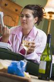 Una mujer joven en su pijama bebiendo vino y frunciendo el ceño en su t — Foto de Stock