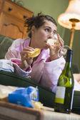 Una mujer joven en su pijama bebiendo vino — Foto de Stock
