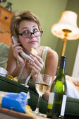 A young woman in her pyjamas on the phone and drinking wine — Stock Photo