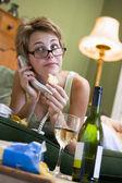 Una mujer joven en su pijama en el teléfono y beber vino — Foto de Stock