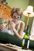 Una mujer joven en su pijama bebiendo vino y fumando — Foto de Stock