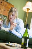 Una mujer joven en su pijama mirando el teléfono, bebiendo wi — Foto de Stock