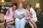 Three young women eating pizza together in their pyjamas — Foto de Stock