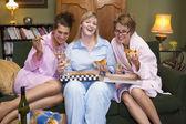 Tres mujeres jóvenes comiendo pizza juntos en su pijama — Foto de Stock