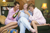 Three young women drinking wine together in their pyjamas — Стоковое фото