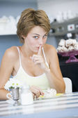 A young woman sitting in a cafe guiltily eating a sweet treat — Stock Photo