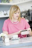 Una giovane donna seduta in un caffè guardando preoccupato nella sua borsetta — Foto Stock