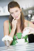 Młoda kobieta, siedząc w kawiarni zalewanie jej herbaty cukru — Zdjęcie stockowe