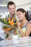 A young man giving flowers to a young woman in a cafe — Stock Photo