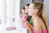 Young women drinking milkshakes in a cafe — Stock Photo