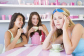 Two young women enjoying a tea party while one sits apart wearin — Stock Photo