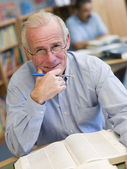 Mature male student studying in library — Stock Photo