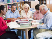 Mature students studying in a library — Stock Photo