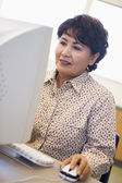 Mature female student learning computer skills — Stock Photo