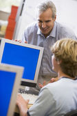 A teacher talks to a schoolboy using a computer in a high school — Stock Photo