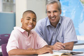 A teacher instructs a schoolboy in a high school class — Foto Stock