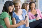 Adolescentes, mirando a un teléfono móvil — Foto de Stock