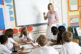A teacher teaching a junior school class — Stockfoto