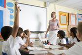 A teacher teaching a junior school class — Stock Photo