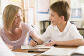 Uno scolaretto seduto con il suo insegnante di classe — Foto Stock