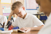 Schoolboy reading a book in class — Stockfoto
