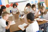 Schoolchildren reading books in class — Stock Photo