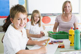 Schoolchildren and their teacher in an art class — Foto Stock
