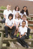School children sitting on benches outside — Stock Photo