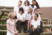 School children sitting on benches outside with their teacher — Stock Photo