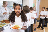Schoolgirl holding plate of lunch in school cafeteria — Stock Photo