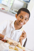 Schoolboy enjoying his lunch in a school cafeteria — Stock Photo