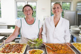 Lunchladies beside trays of food in school cafeteria — Stock Photo