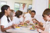 Alunos apreciando seu almoço em uma cantina de escola — Foto Stock