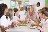 Teacher and schoolchildren enjoying their lunch in a school cafe — Foto Stock