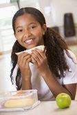 Schoolgirl enjoying her lunch in a school cafeteria — Stock Photo