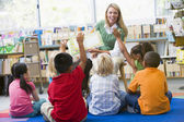 Kindergarten teacher reading to children in library — Stok fotoğraf