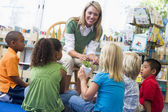Kindergarten teacher and children looking at seedling in library — Stock Photo