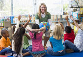 Kindergarten teacher and children with hands raised in library — Stok fotoğraf