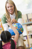 Kindergarten teacher and children looking at globe — Stock Photo