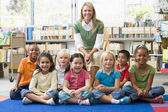 Kindergarten teacher sitting with children in library — Stock Photo