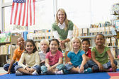 Kindergarten teacher sitting with children in library — ストック写真