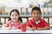 Kindergarten children sitting at desk and writing in classroom — ストック写真