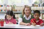 Kindergarten teacher helping students with writing skills — Stockfoto