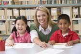 Воспитатель детского сада, помогая студентам изучать навыки письма — Стоковое фото