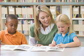 Kindergarten teacher helping students with reading skills — ストック写真