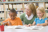 Kindergarten teacher helping students with reading skills — Stok fotoğraf