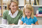 Kindergarten teacher helping student with reading skills — Foto Stock